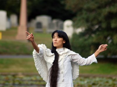 A human angel in Brooklyn's Green-Wood Cemetery gestures skyward at its annual Angels and Accordions Event