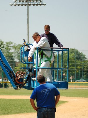 Workers employed by the New York City Department of Design and Construction working to safely recover wild baby Quaker Parrots at the Throggs Neck Little League baseball field, June 7, 2007
